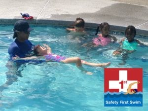 Tukz Taaca teaching a swim lesson to young children in a pool