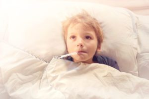 picture of small boy in bed with a thermometer in his mouth