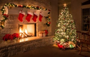 a picture of a fireplace hung with Christmas stockings and a decorated tree next to it